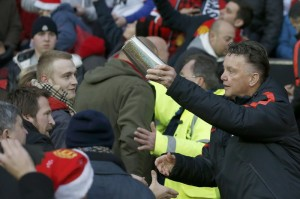 Manchester United manager Louis van Gaal hands out Christmas presents to fans before their English Premier League soccer match against Newcastle at Old Trafford in Manchester